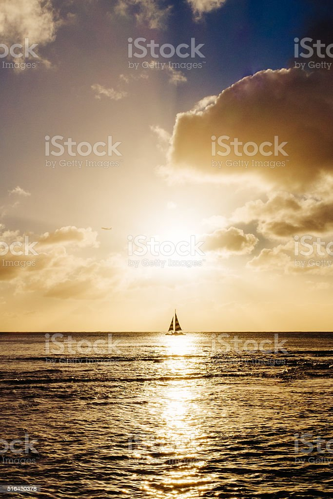 Boat sailing and plane taking off at sunset stock photo