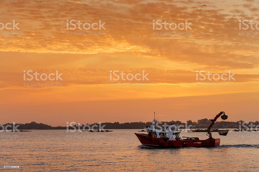 Barco navegando al atardecer stock photo