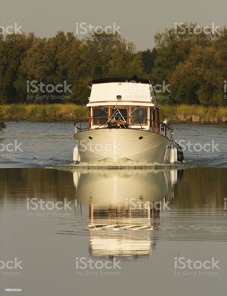 Boat sailing in a quiet river royalty-free stock photo