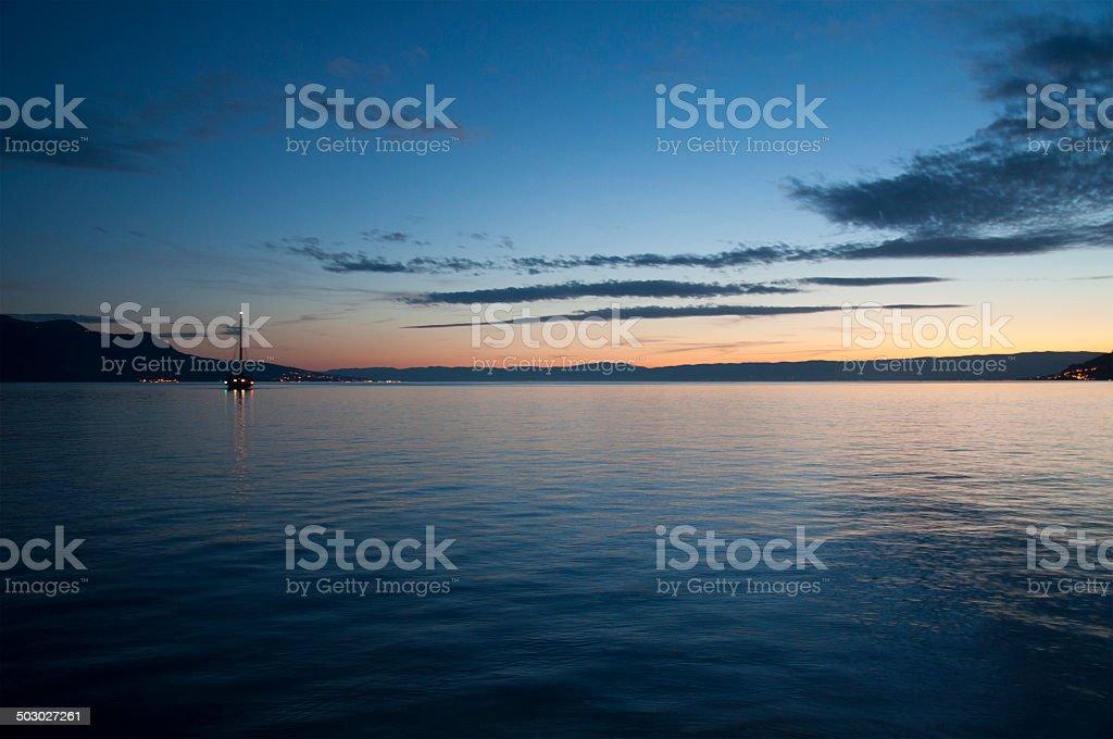 Boat Sailing in Lake Geneva at Sunset stock photo