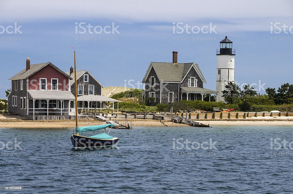 A boat sailing on a lake in front of two beach houses stock photo