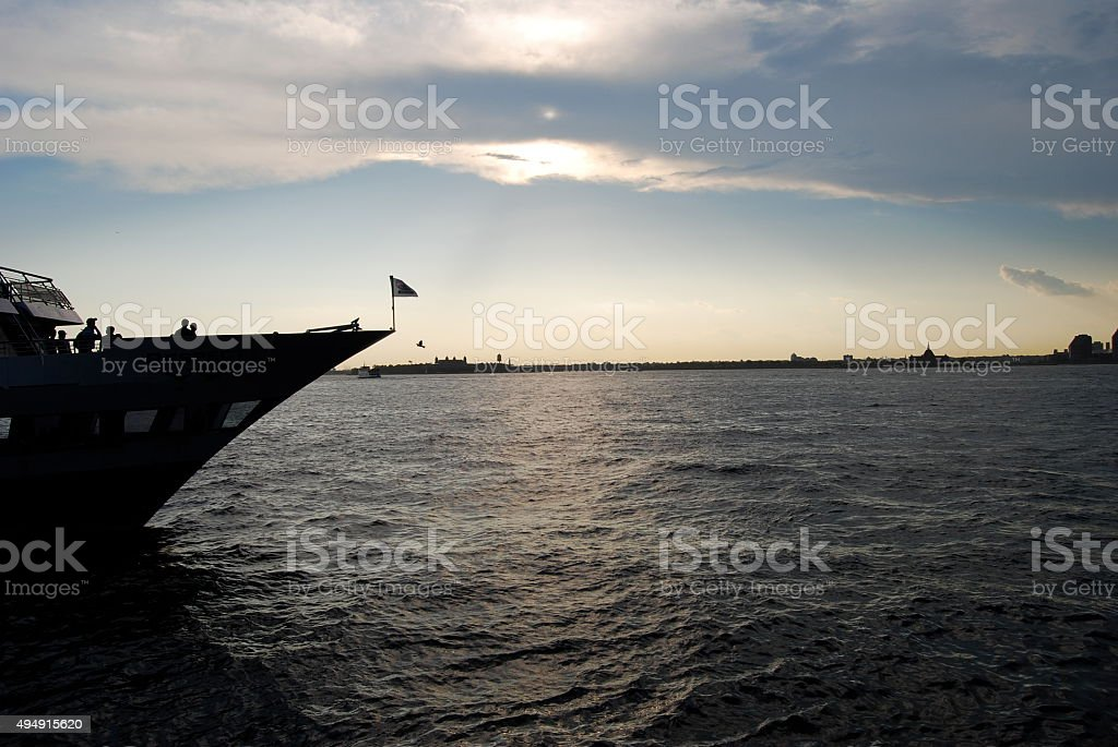 Boat silhouette against a blue cloudy sky stock photo