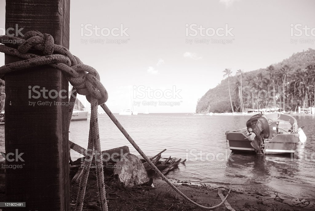boat tied to pole at bay royalty-free stock photo