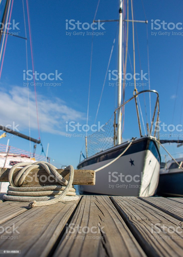 Boat tied to wooden dock stock photo