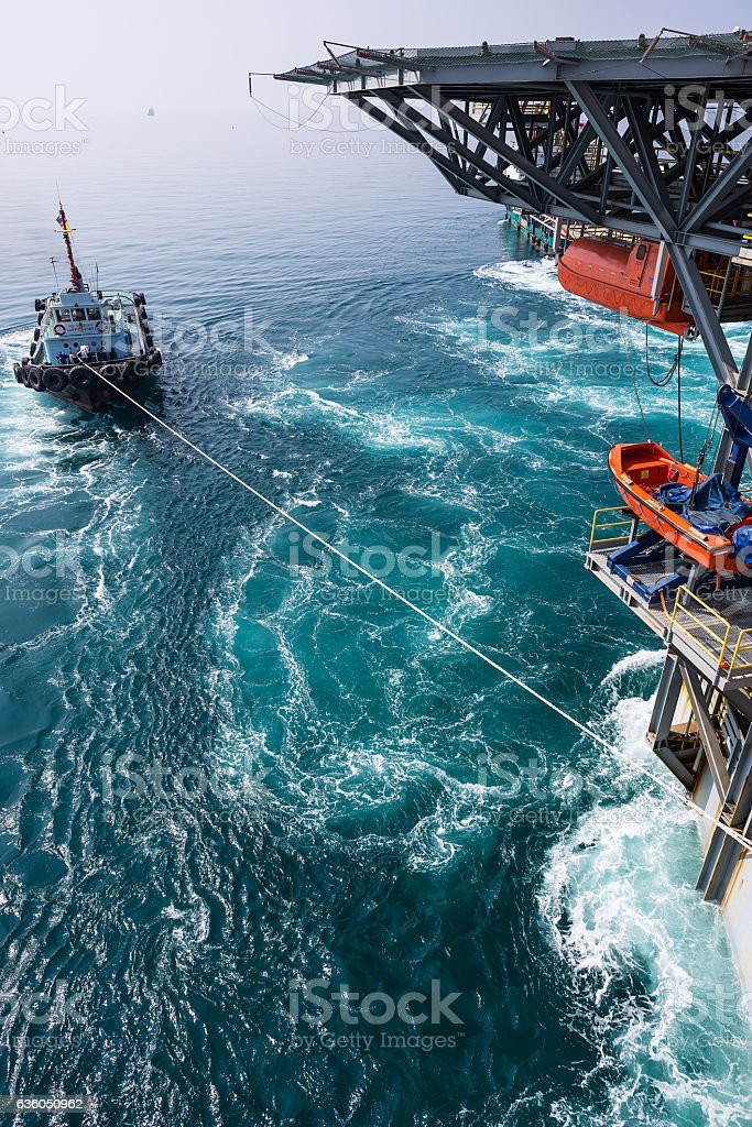 Boat towing jack up oil and gas rig stock photo