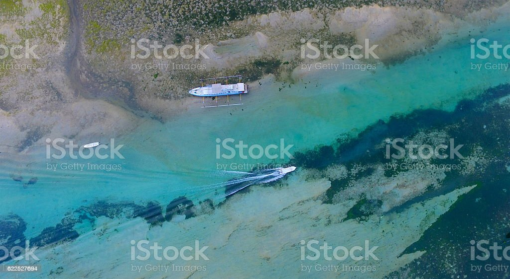 Boat travelling along shallow tropical waterway stock photo