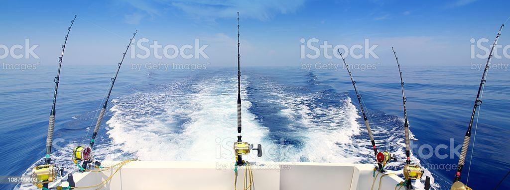 Boat trolling the sea with rod and reels stock photo