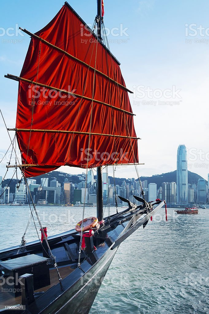 Boat with a red sail in Victoria Harbour in Hong Kong stock photo
