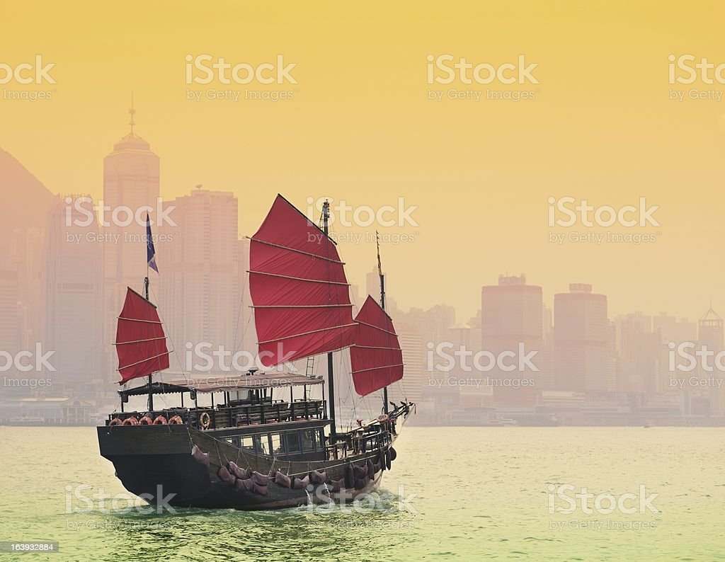 Boat with red sails sailing in Hong Kong harbor stock photo