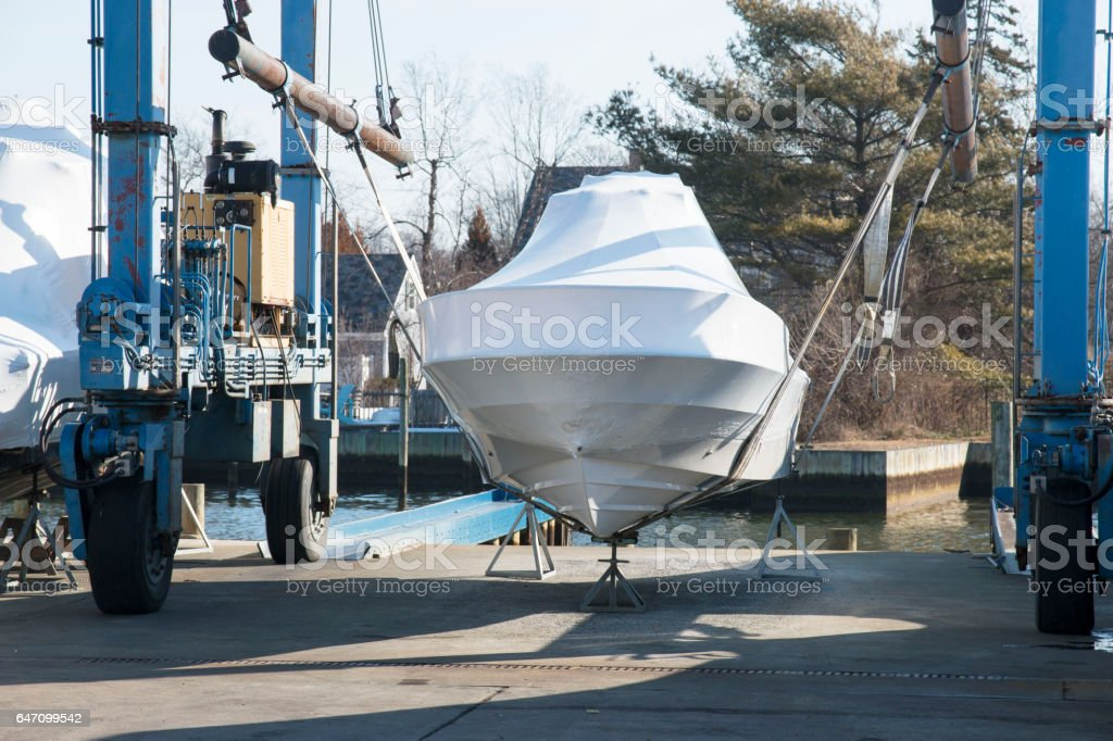 Boat wrapped up for winter and on a sling stock photo