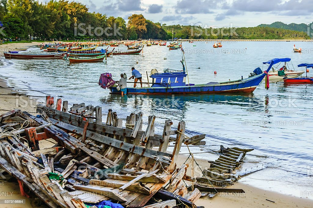 Boat wreck & long-tail boats, Phuket, Thailand stock photo