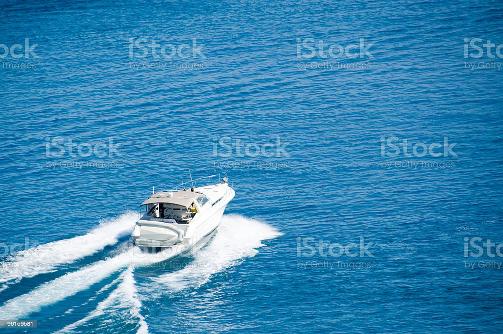 Boater heading out on blue waters. stock photo