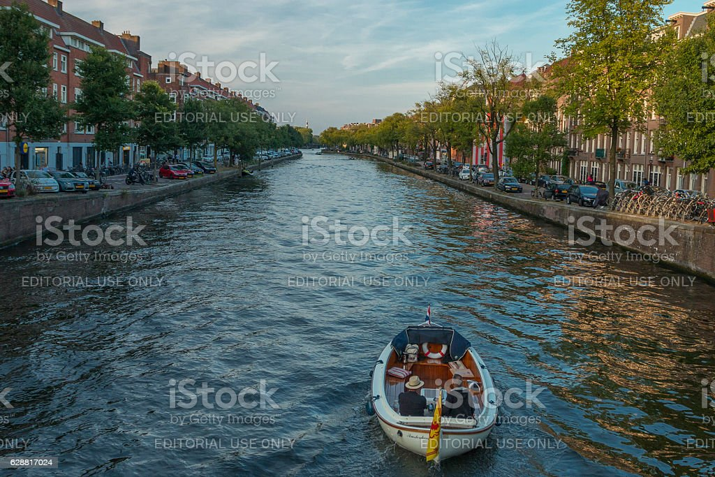 Boaters on canal in Amsterdam. stock photo