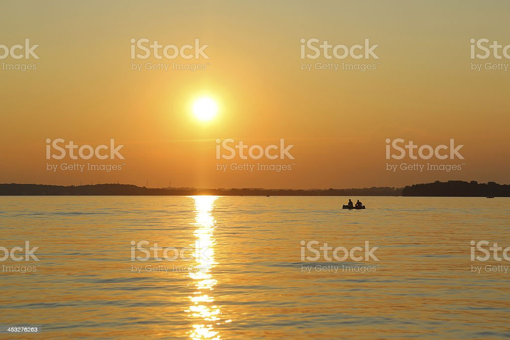 Boaters on lake at sunset royalty-free stock photo