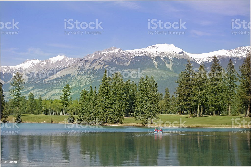 Boaters on Mountain Lake with Dramatic Surroundings royalty-free stock photo