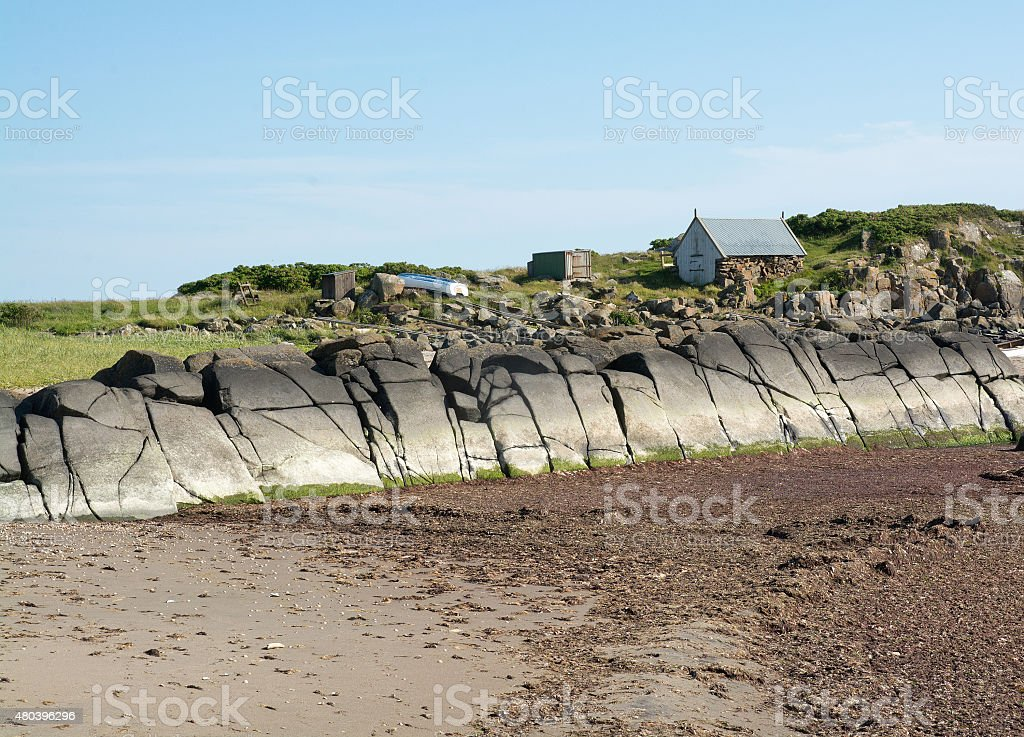 Boathouse and boat by interesting rock shape stock photo