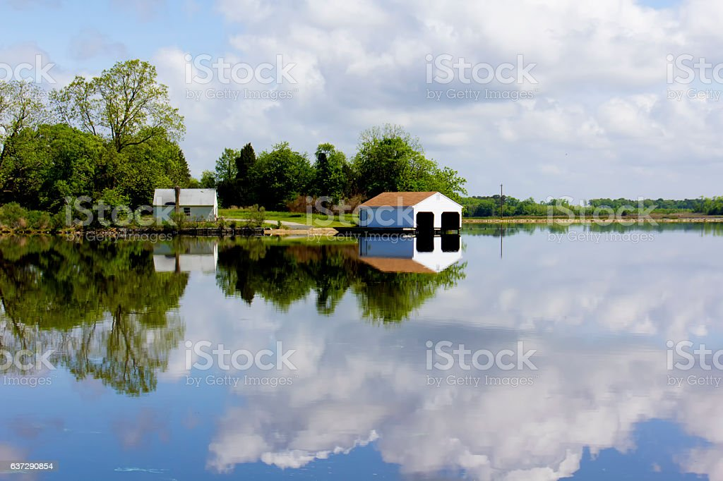 Boathouse reflected in river stock photo