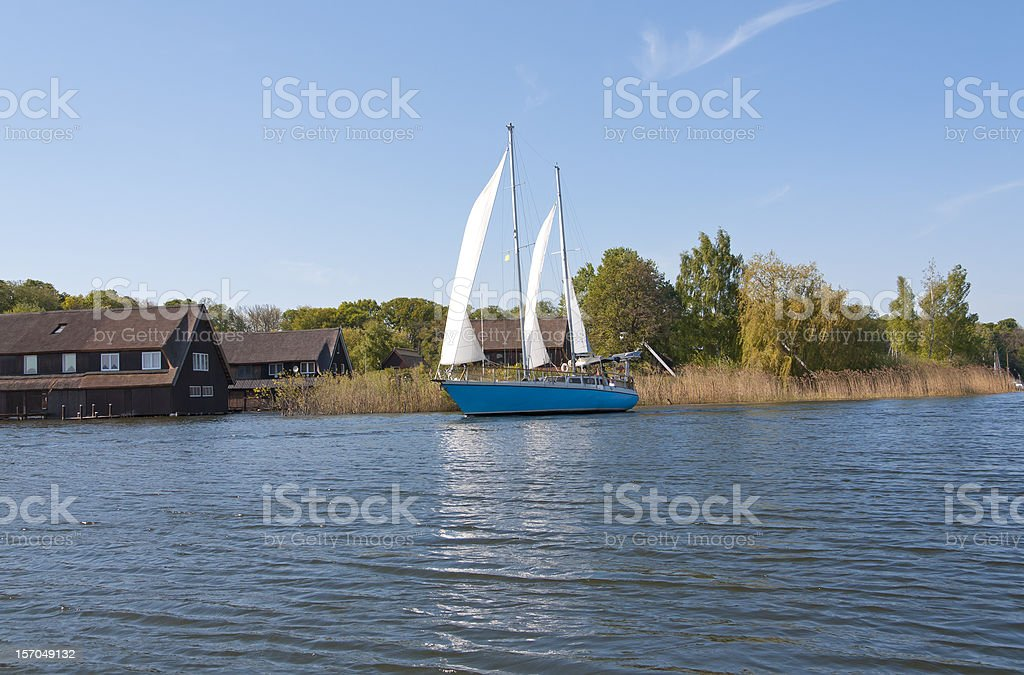 Boathouses and a sailing ship on the Mueritz Lake stock photo