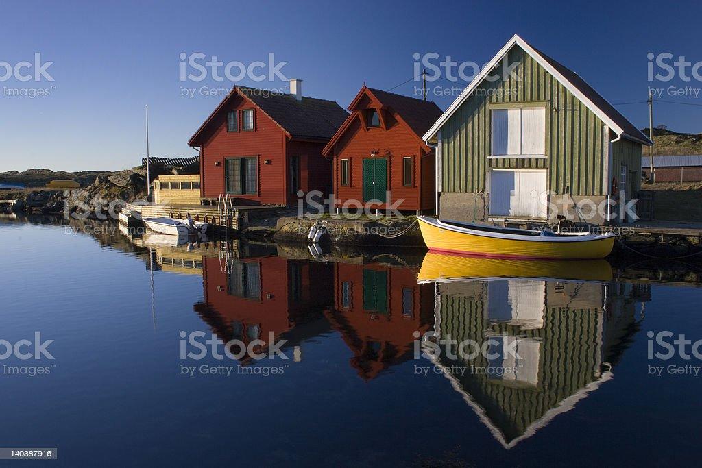 Boathouses with reflection, Kvtsoey Island, Norway. stock photo