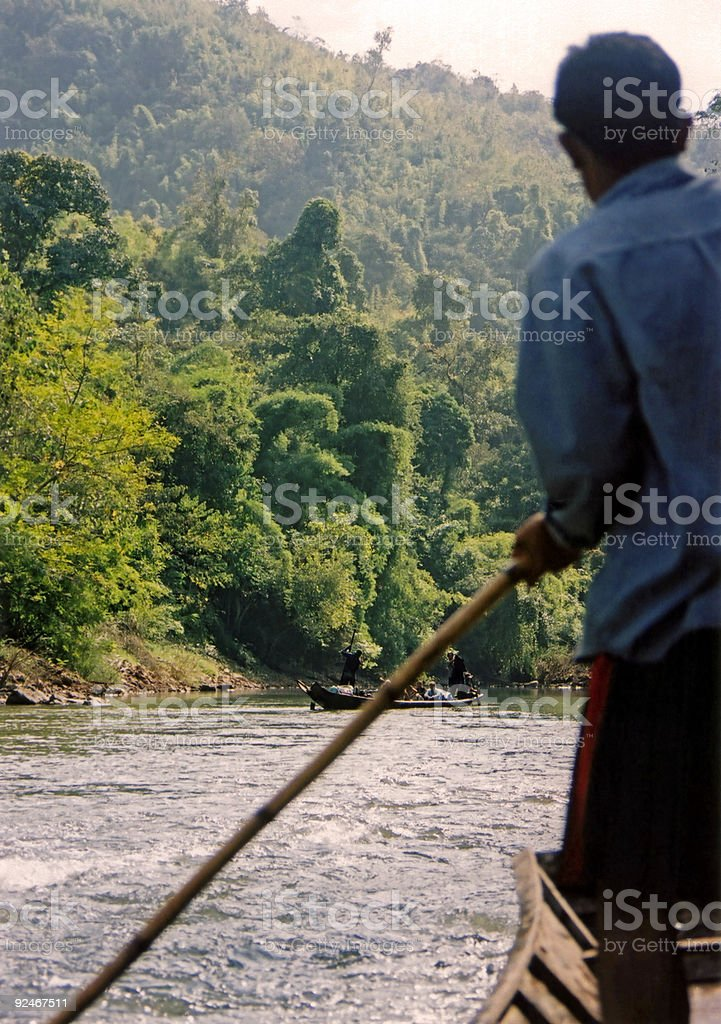 boatman navigating river rapids laos royalty-free stock photo