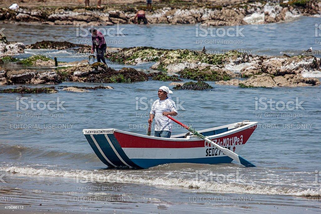 Boatman rowing off Barranca Beach in Peru stock photo