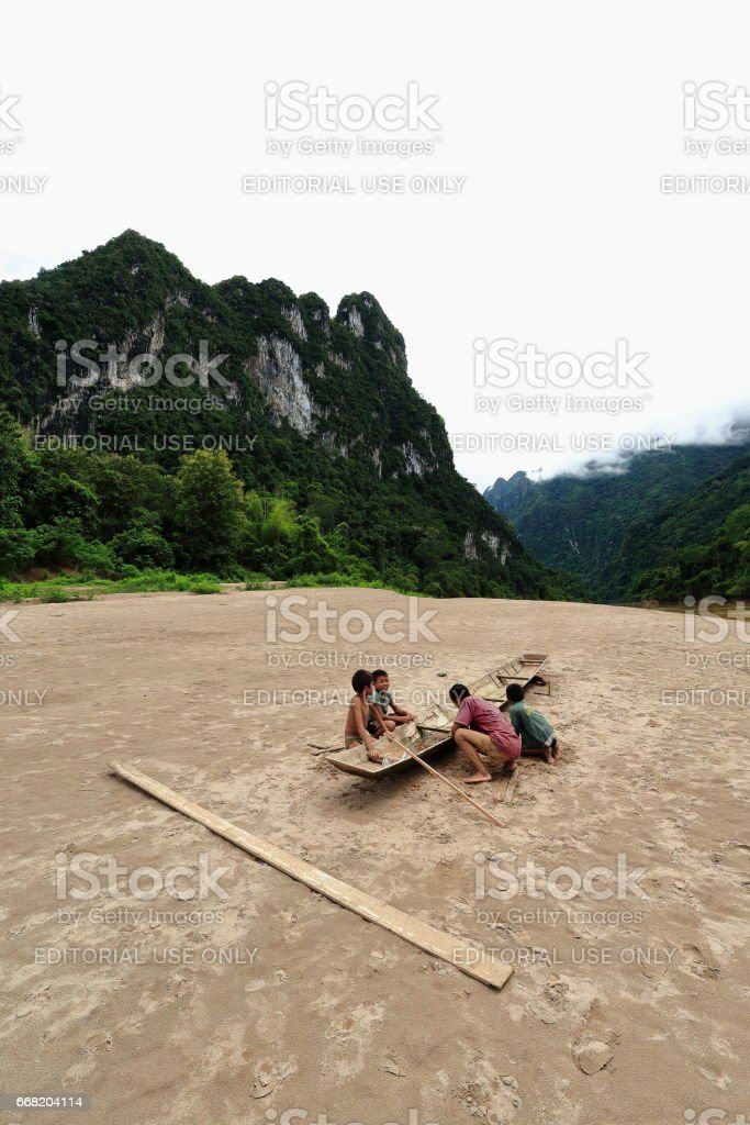 Boatman-rowboat-NamOu river bank-SopChem downstream from MuangKhua. Luang Prabang province-Laos. 3969 stock photo