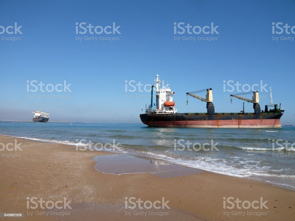 Boats aground at Saler beach, Valencia, Spain. Container ship after running aground. Cargo ship Bsle Sunrise of Panama and Celia of Saint Johns run aground after a gale wind storm. stock photo