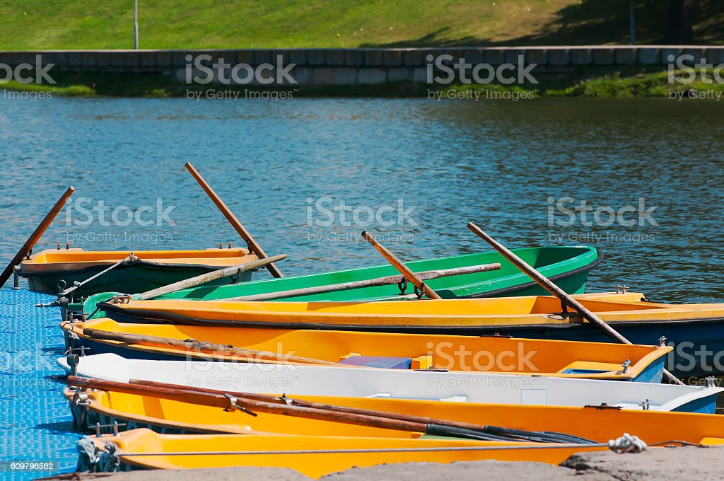 boats and catamarans are on the pier near the river stock photo