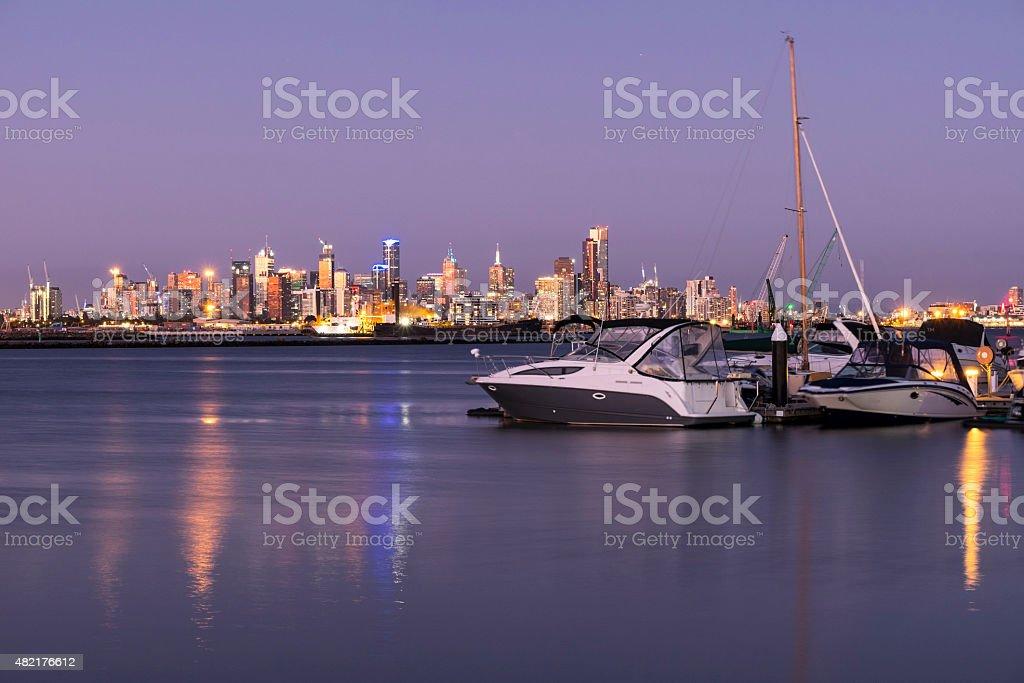 boats and city skyline at twilight stock photo