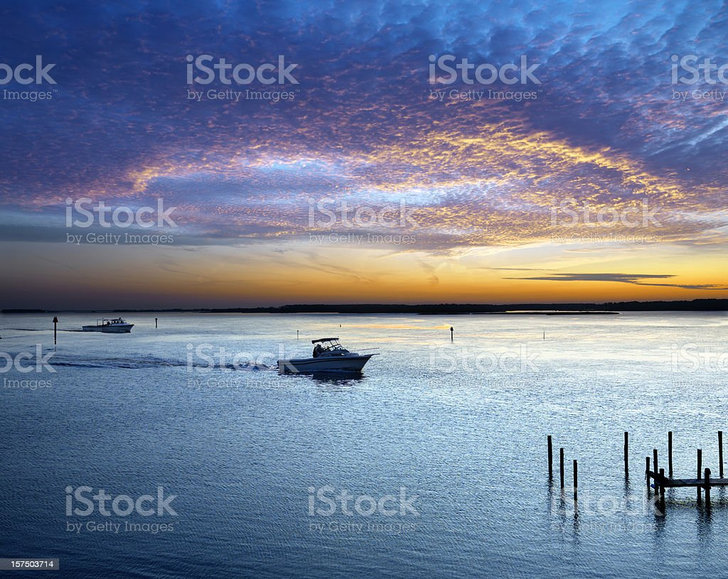 Boats and sunset on the water stock photo