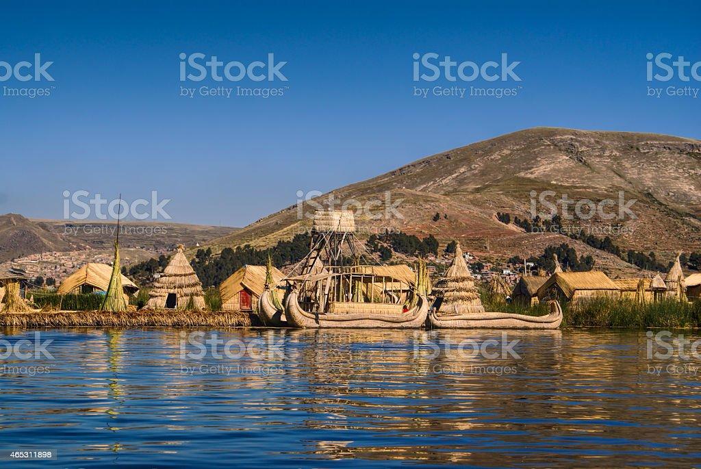 Boats and tribal houses at Islas Flotantes stock photo