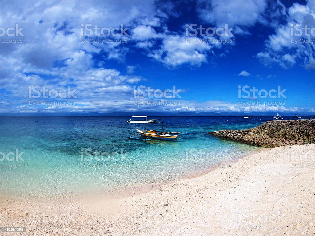Boats and white sand beach in Moalboal stock photo