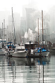 boats and yachts in a foggy day in harbour marina
