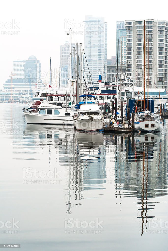 boats and yachts in a misty day in harbour marina stock photo