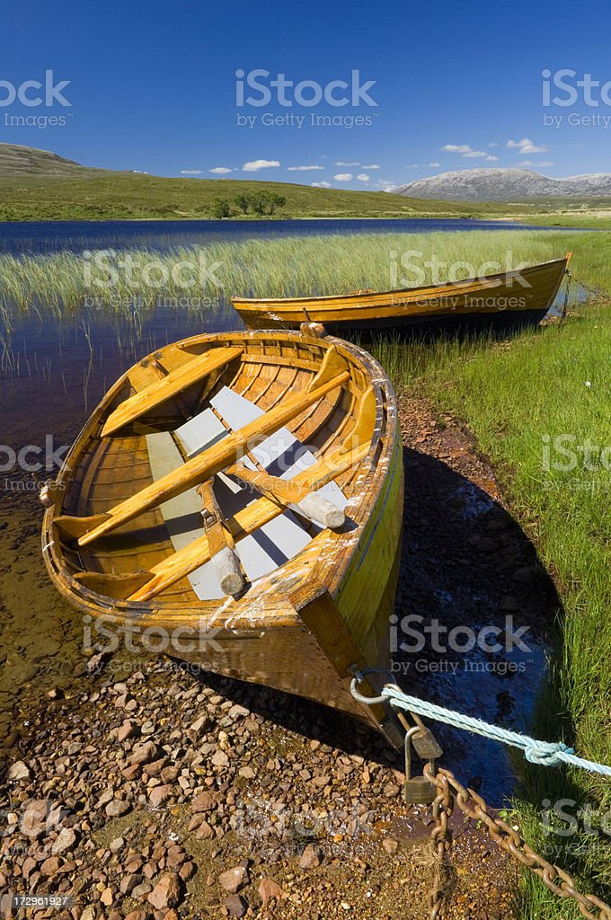 Boats at edge of Scottish loch stock photo