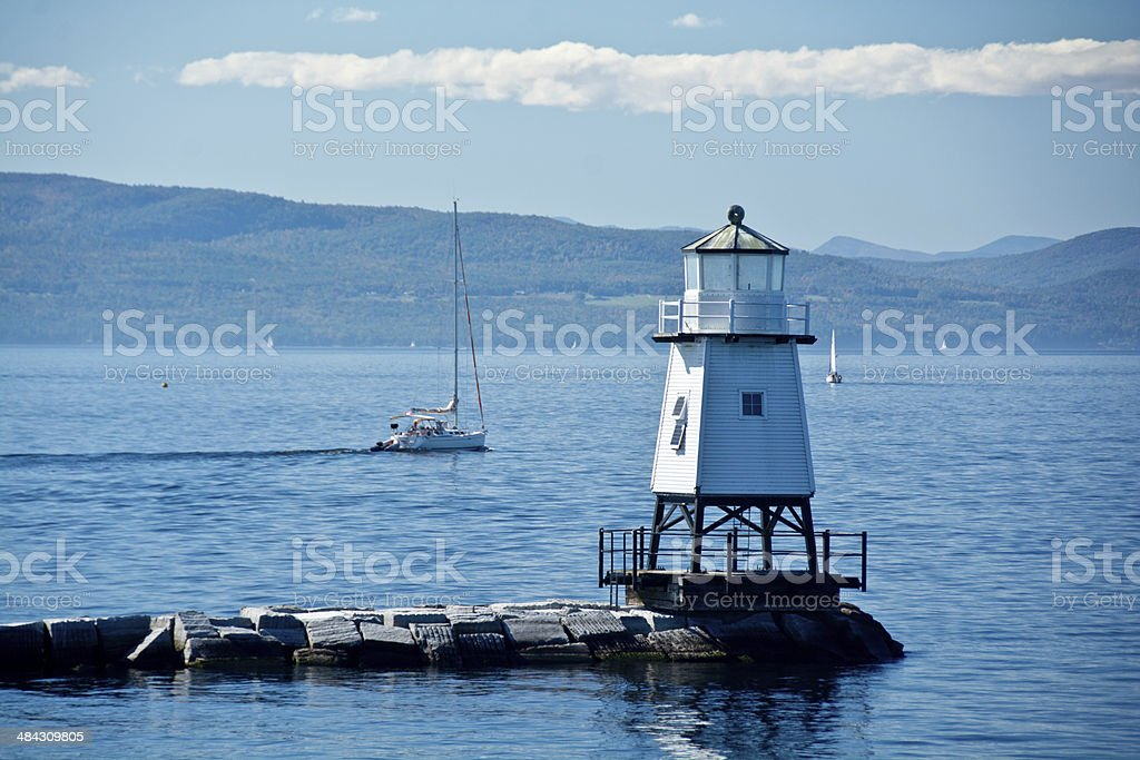 Boats behind Burlington light house stock photo
