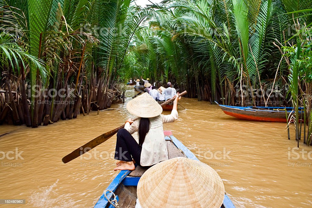 Boats in a line rowing down the Mekong river stock photo