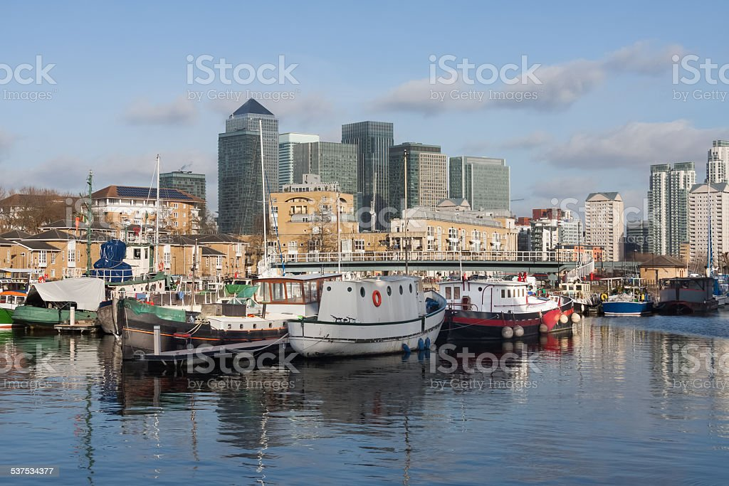 Boats in the Greenland Dock with Canary Wharf in the background stock photo