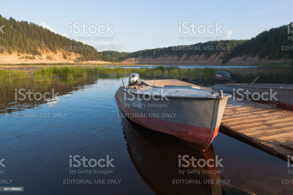 Boats in the summer evening at a wooden pier on the Sukhona River in the tract of Opoki stock photo