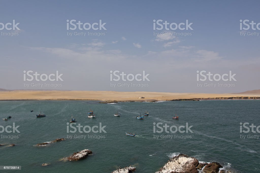 Boats in the water close to the beach. Perfect place to see tropical desert, wide cliffs and coloful beaches on the rocky islands and national reserve. Small islands near the town of Paracas. stock photo