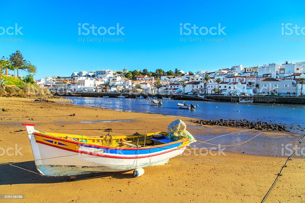 Boats in warm sunset light on the beach in Portimao, Portugal stock photo