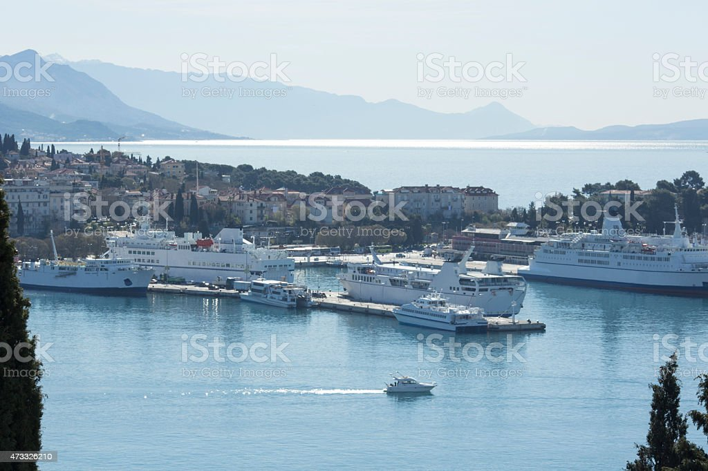 Boats leave harbour under sunny skies stock photo