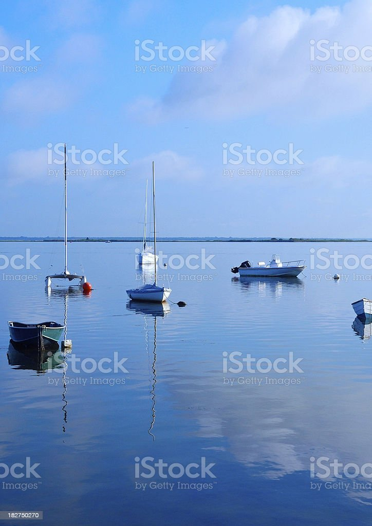 Boats moored in early morning on a placid bay stock photo