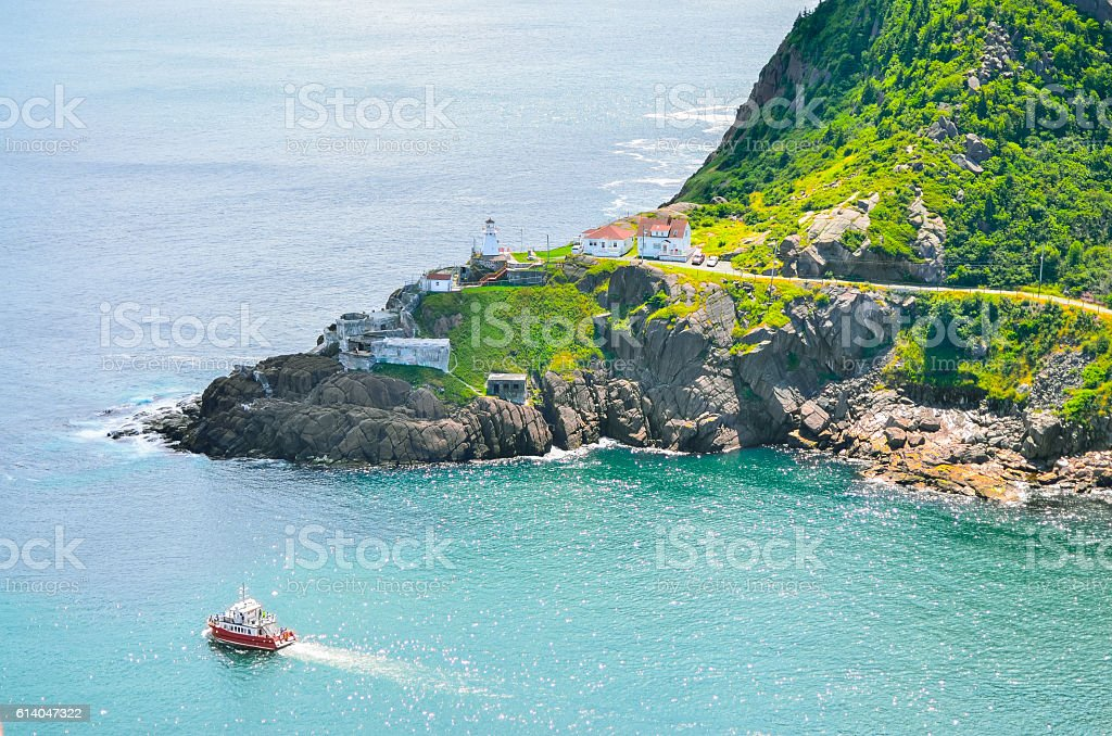 Boats motor past Fort Amherst.  Rugged coastline and Atlantic ocean. stock photo