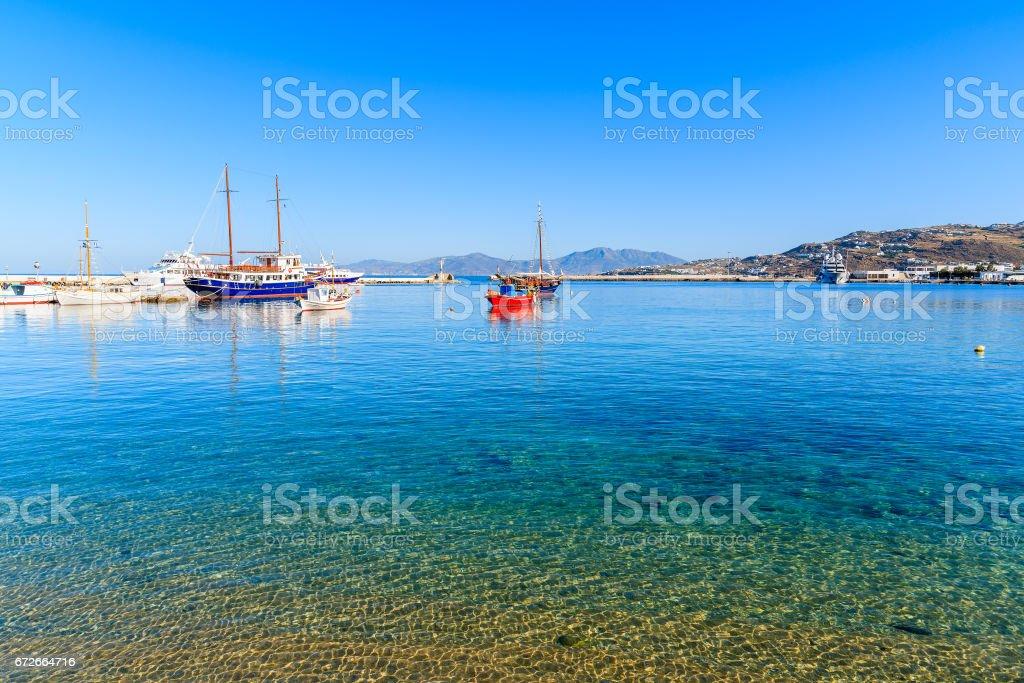 Boats on azure sea in Mykonos port, Cyclades, Greece stock photo