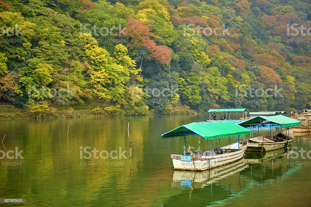 Boats on Katsura river at fall in Arashiyama, Kyoto stock photo