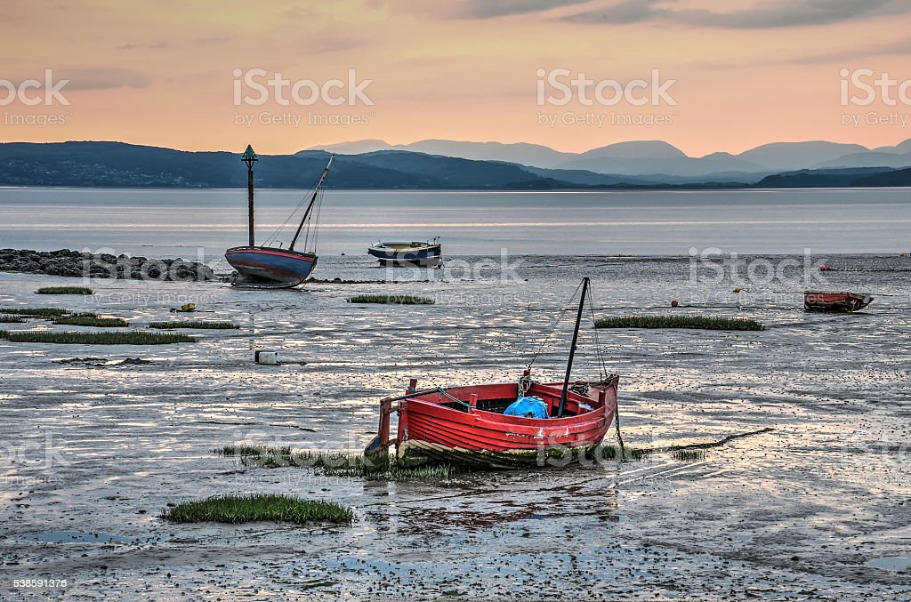 Boats on the beach at sunset stock photo