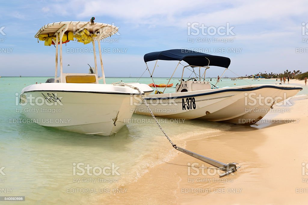 Boats on the beach waiting for vacationers in Aruba stock photo