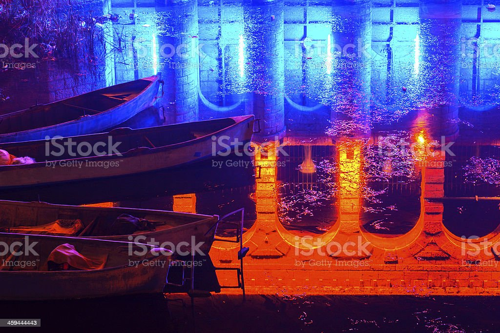 boats on water with stone bridge's reflection stock photo