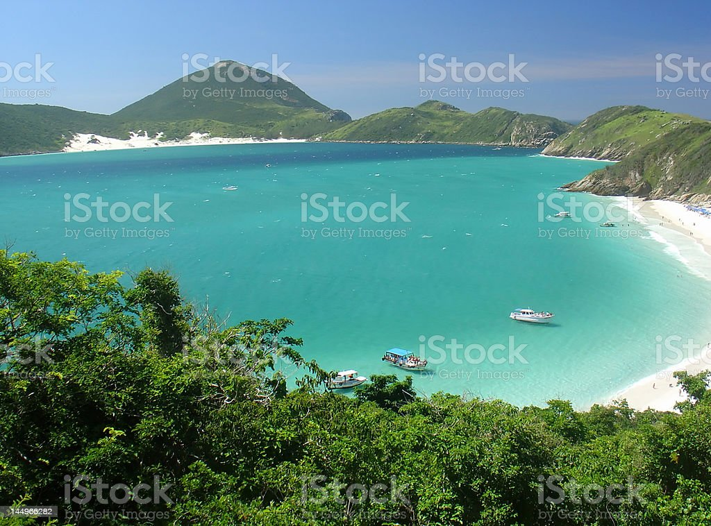 Boats over a crystalline turquoise sea in Arraial do Cabo, stock photo